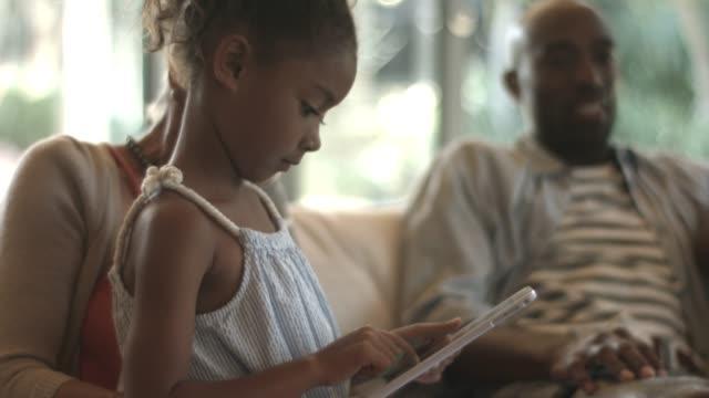 vidéos et rushes de woman talking with granddaughter using tablet pc - prendre sur les genoux