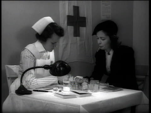 1941 woman talking with nurse at table / Boston, Massachusetts, United States