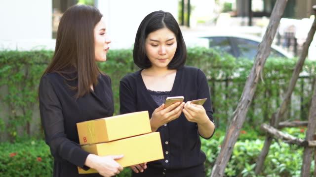 vídeos y material grabado en eventos de stock de mujer hablando con asociación prepara envases para enviar a cliente - haz de luz