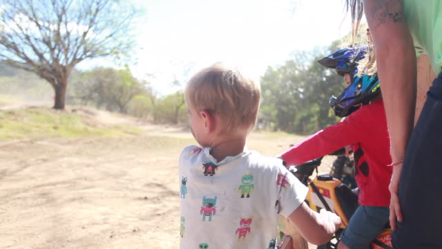 vídeos y material grabado en eventos de stock de a woman talking with two young boys as they are watching people go around the dirt bike track and then the woman and one of the young boys on a dirt bike walk towards the dirt bike track getting ready for a race - kelly mason videos