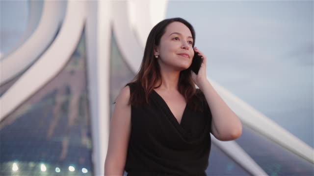 """vídeos de stock, filmes e b-roll de """"ms a woman talks on a mobile phone with cathedral metropolitana in background / brasilia, brazil"""" - catedral"""