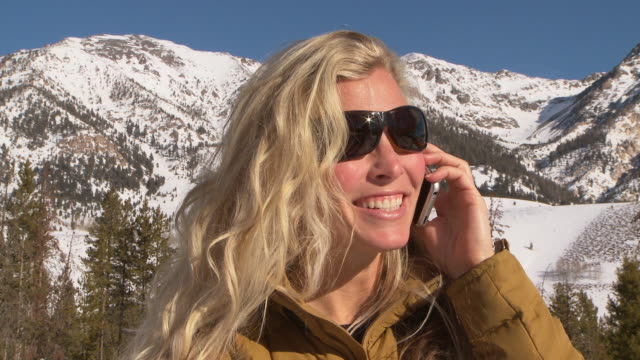 Woman talks on cell phone outdoors on snow covered hills / Blaine County, Idaho, United States