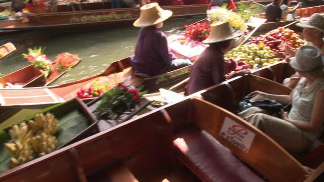 MS HA PAN Woman tasting fruit on boat on Damnoen Saduak floating market, Bangkok, Thailand