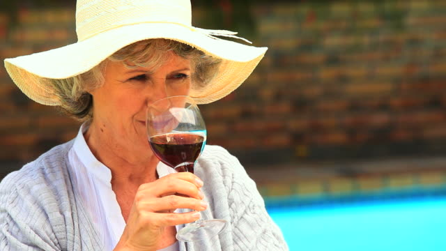Woman tasting red wine outdoors / Cape Town, Western Cape, South Africa