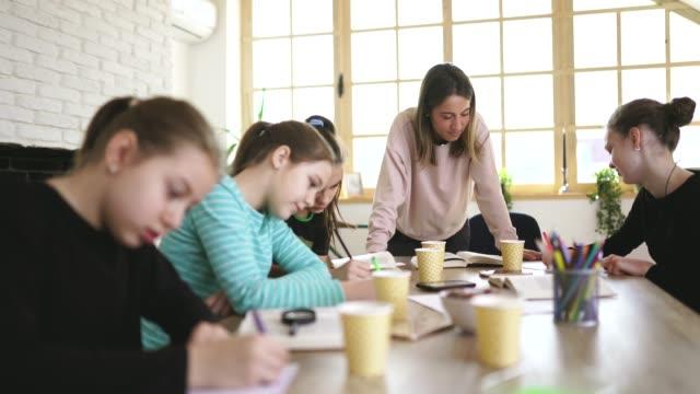 vidéos et rushes de femme enseignant et filles ensemble sur la classe privée - cours de mathématiques