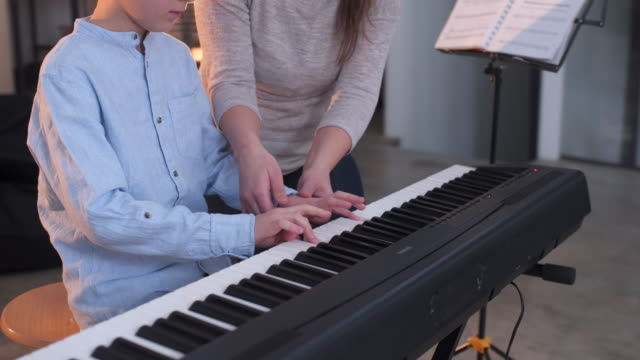 woman teaching a little boy how to play piano - piano stock videos & royalty-free footage