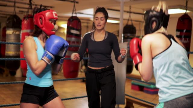 vídeos de stock, filmes e b-roll de mulher ensinar boxe - posição de combate
