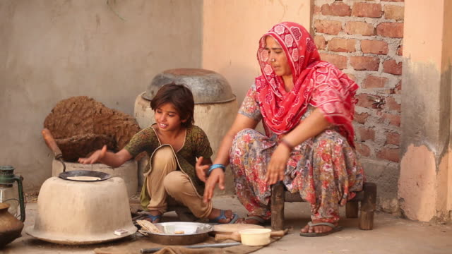 Woman teaching her daughter to cook, Faridabad, Haryana, India
