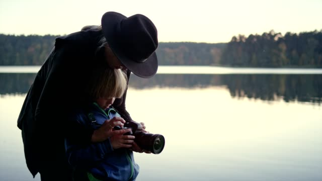 woman teaching her son how to use a camera. autumnal landscape - photographer stock videos & royalty-free footage