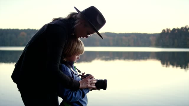 woman teaching her son how to use a camera. autumnal landscape - named wilderness area stock videos & royalty-free footage
