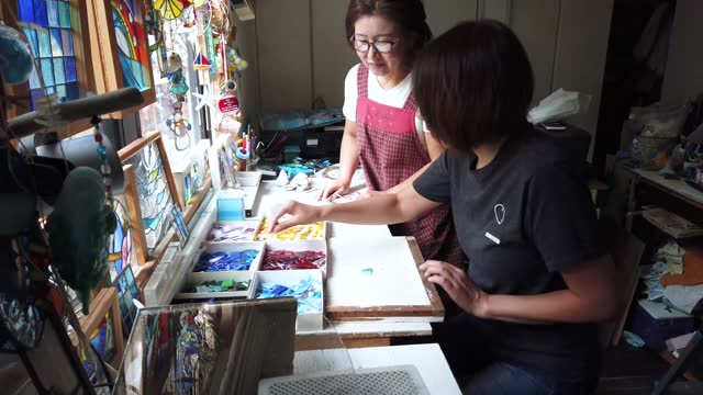 a woman teaching her students how to make stained glass in her home studio - short sleeved stock videos & royalty-free footage