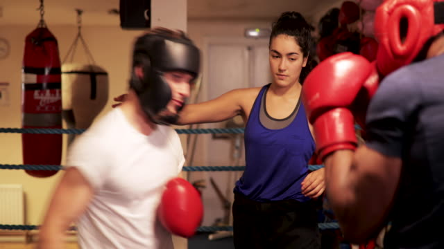 woman teaching men to box - femmina con gruppo di maschi video stock e b–roll