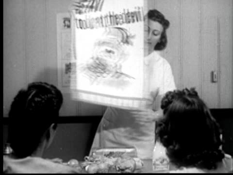 1945 MS Woman teaching nutrition class and showing poster with caricature of Hitler which reads Eat to beat the Devil/ Sylacauga, Alabama