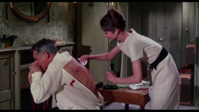1963 a woman (audrey hepburn) teases and flirts with man (cary grant) as she cleans his wound - wounded stock videos & royalty-free footage