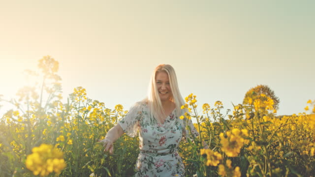 slo mo woman teasing in the canola field - front view stock videos & royalty-free footage