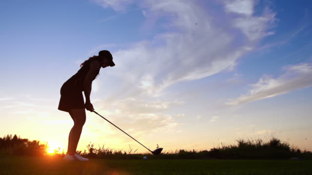 woman tees off at dawn - green golf course stock videos and b-roll footage