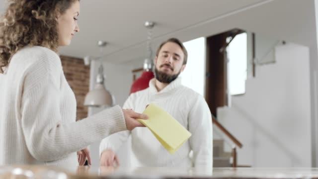 vidéos et rushes de femme disant homme pour nettoyer une cuisine - corvée domestique