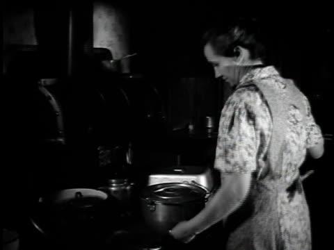 vídeos y material grabado en eventos de stock de 1923 ms woman tending fire in wood stove / united states - 1923