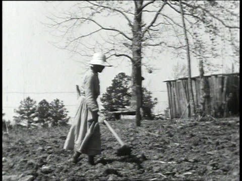 1939 MS woman tending garden / Lowndes County, Alabama, United States