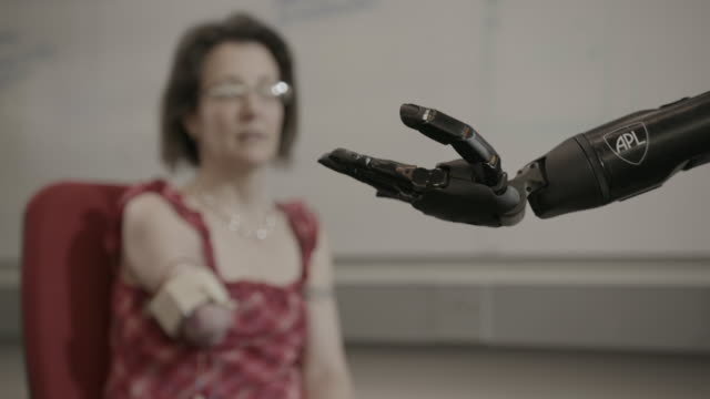 woman tests fingers on bionic arm - artificial limb stock videos & royalty-free footage