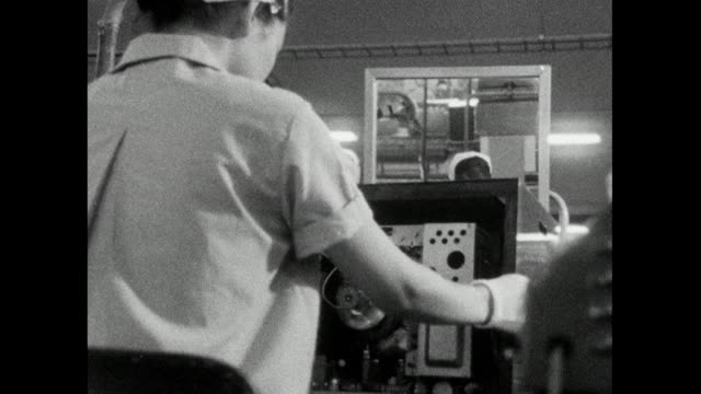 woman tests television set in japanese electronics factory; 1966 - 科学技術点の映像素材/bロール