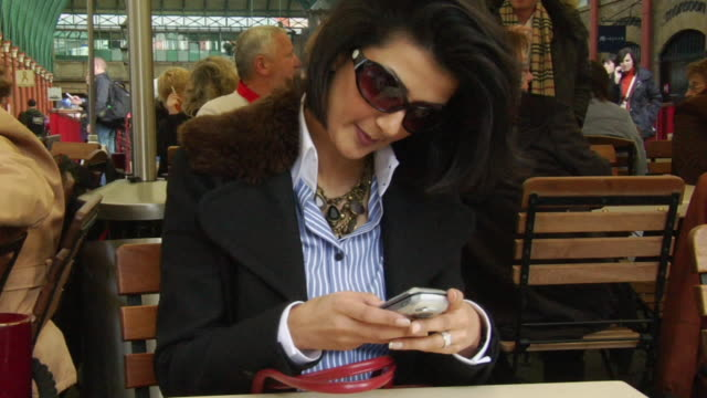 CU, Woman text massaging in outdoors cafe, Covent Garden, London, England