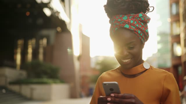 Woman text messaging at sunset, happy, lens flare