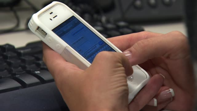 woman text messaging at workplace - text messaging video stock e b–roll
