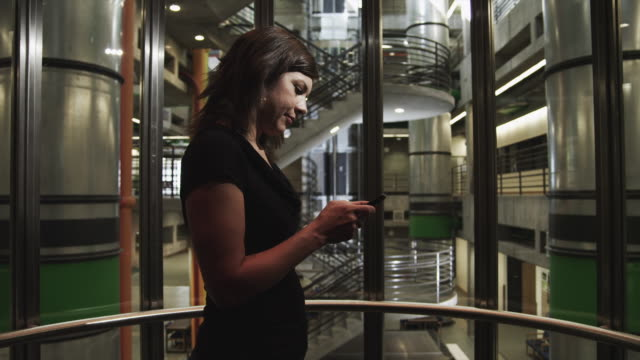 ms pov woman text messaging in modern elevator in office building / orem, utah, usa - 35 39 jahre stock-videos und b-roll-filmmaterial