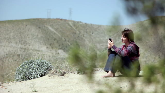 ws pan woman text messaging on smart phone in desert / palm springs, california, usa - 前ボケ点の映像素材/bロール