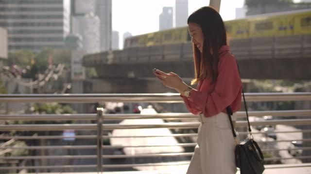 frau text-messaging auf smartphone zu fuß zur arbeit in der stadt - nur junge frauen stock-videos und b-roll-filmmaterial