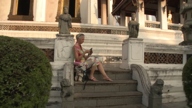 WS ZI MS Woman text messaging on temple steps, Wat Phra Kaew (Temple of the Emerald Buddha), Bangkok, Thailand