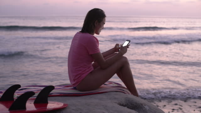 vídeos de stock, filmes e b-roll de ms woman texting on her phone after surfing - sentar