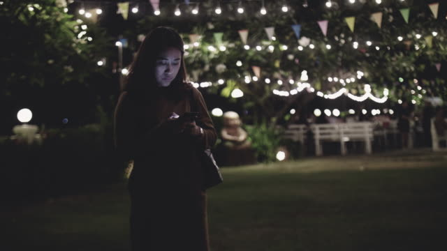 woman texting on mobile phone in the city at night - internet dating stock videos and b-roll footage