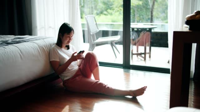 彼女の寝室で床に座っている間に携帯電話でテキストメッセージ - 寝室点の映像素材/bロール