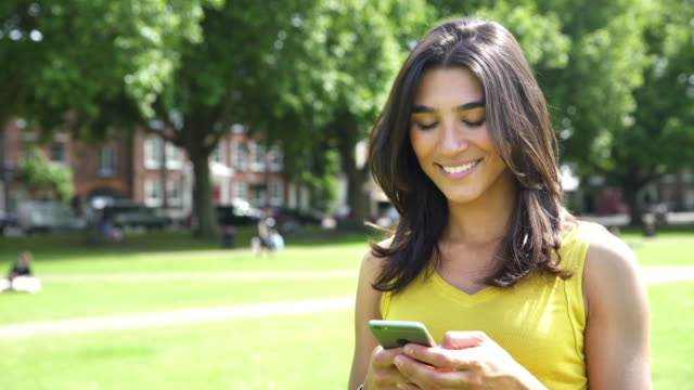 Woman texting, reading, responding and smiling with smart phone