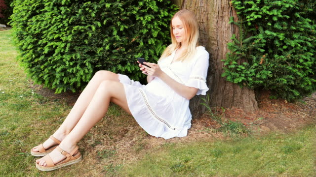 woman texting under a tree. slow motion - picking up stock videos & royalty-free footage