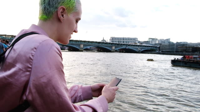 Woman texts on her cellphone along the Thames River in London, England at sunset with a London skyline in the background.