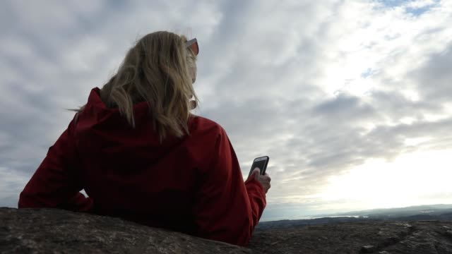 woman texts while relaxing against rock - ascentxmedia stock videos & royalty-free footage