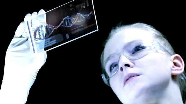 donna scienziato è analizzare la struttura del dna. - scienziata video stock e b–roll