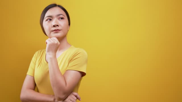 woman thinking over isolated yellow background - plain background stock videos & royalty-free footage