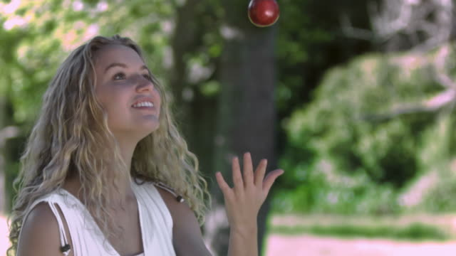 Woman throwing an apple in slow motion