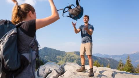 stockvideo's en b-roll-footage met woman throwing backpack to man in mountains - rugzak