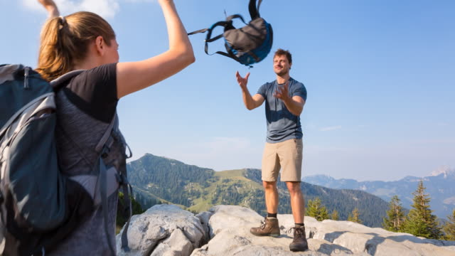 woman throwing backpack to man in mountains - catching stock videos & royalty-free footage