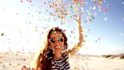 Woman throwing confetti in slow motion on the beach