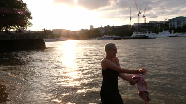 A woman throwing her jacket in the air while dancing in the Thames River in London, England during sunset.