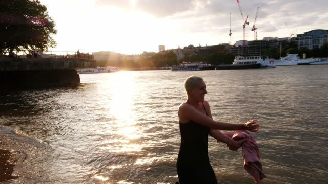 a woman throwing her jacket in the air while dancing in the thames river in london, england during sunset. - naga river stock videos and b-roll footage
