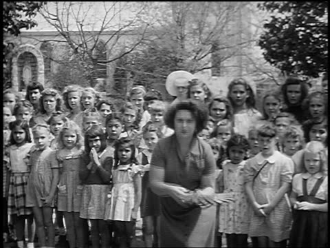 B/W 1955 woman throwing knives at camera with crowd of young girls in background outdoors
