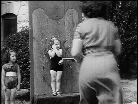 vídeos de stock, filmes e b-roll de b/w 1955 rear view woman throwing knives at small girl standing against board outdoors - faca faqueiro