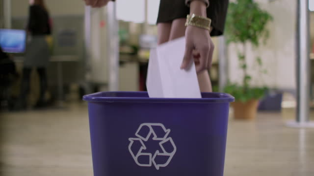 vídeos y material grabado en eventos de stock de cu selective focus woman throwing out papers into recycling basket in office, appleton, wisconsin, usa - reutilizable